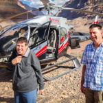 two men in front of a helicopter at the grand canyon